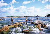 Iriri River, Amazon, Brazil. Ecotourists from Tataquara lodge bathing in the rapids of a remote part of the river.