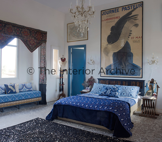 In the master bedroom a vintage French poster hangs above a bed covered with fabrics from Mali and Morocco