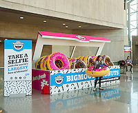 Attendees pose for selfies in front of BigMouth's world's largest box of donuts on display at the 114th North American International Toy Fair in the Jacob Javits Convention center in New York on Sunday, February 19, 2017.  The four day trade show with over 1000 exhibitors connects buyers and sellers and draws tens of thousands of attendees.  The toy industry generates over $26 billion in the U.S. alone and Toy Fair is the largest toy trade show in the Western Hemisphere. (© Richard B. Levine)