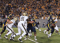 WVU running back Noel Devine (7) heads upfield behind the block of Don Barclay on Pitt's Greg Romeus (91). The West Virginia Mountaineers defeated the Pittsburgh  Panthers 19-16 on November27, 2009 at Mountaineer Field at Milan Puskar Stadium, Morgantown, West Virginia.