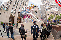 "Visitors observe Jeff Koons' sculpture ""Seated Ballerina"" unveiled in Rockefeller Plaza in New York on Friday, May 12, 2017. The 45-foot tall inflatable nylon sculpture is based on a small porcelain figurine. This is Koons' third installation in Rockefeller Plaza with ""Puppy"" and ""Split-Rocker"" being show in 2000 and 2014 respectively. The sculpture will be on view until June 2 and will be deflated during inclement weather. © Richard B. Levine)"