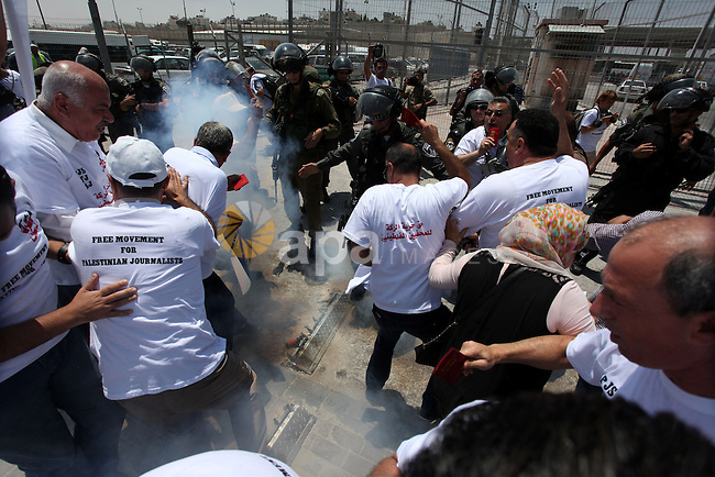 Israeli soldiers attack Palestinian journalists during a demonstration demanding for the free movement of journalists and Palestinians at the Qalandia checkpoint between Ramallah and Jerusalem, in the occupied West Bank on July 17, 2013. Photo by Issam Rimawi