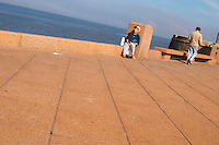 A woman sitting drinking mate herbal tea and a man walking on the pavement, on the riverside seaside walk along the river Rio de la Plata Ramblas Sur, Gran Bretagna and Republica Argentina Montevideo, Uruguay, South America