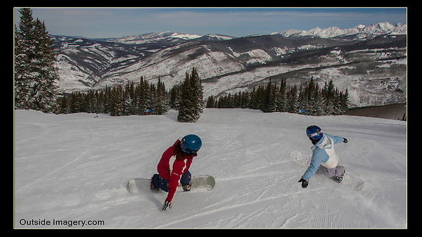 Stage Technique.<br /> Here, I composed my 'stage' and asked my two daughters to pass by me. As soon as I saw them in the corner of my eye, I started exposing. I kept my camera stable. If I followed the action (snowboarders) my composition would quickly decompose.<br /> Vail Ski Area, Colorado, USA.