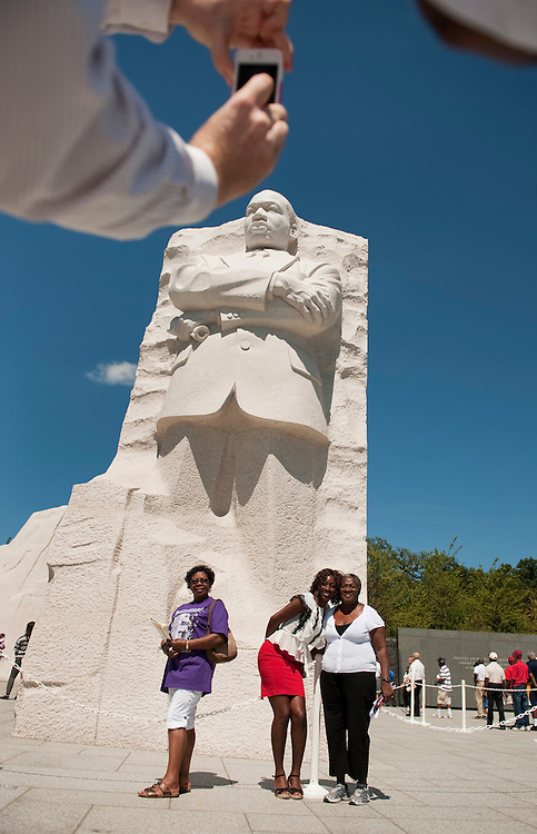 UNITED STATES - AUGUST 23:  Visitors pose for pictures at the base of the Martin Luther King Jr. Memorial, located on the Tidal Basin.  The Memorial is open to the public and the official dedication ceremony will take place on August 28.  (Photo By Tom Williams/Roll Call)