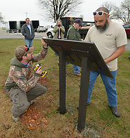 NWA Democrat-Gazette/ANDY SHUPE<br /> Eric Casson (left) and Angel Cruz, both sign and marking technicians with the city of Springdale Public Works Department, work together Wednesday, March 28, 2018, to install an informational sign near a bioswale and filtration basin at the city's Recycling Drop-Off Center on Lowell Road. The structure was constructed through a collaboration between the city and the University of Arkansas Cooperative Extension Service with support from the Urban Forestry Program of the Arkansas Forestry Commission and the U.S. Forest Service. The sign describes the function of the structure as a way to manage water runoff and filter pollutants before they enter the watershed.
