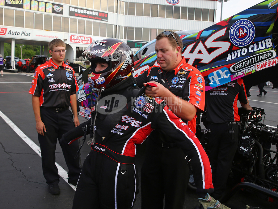 May 15, 2015; Commerce, GA, USA; A crew member helps NHRA funny car driver Courtney Force put on her safety gear during qualifying for the Southern Nationals at Atlanta Dragway. Mandatory Credit: Mark J. Rebilas-USA TODAY Sports