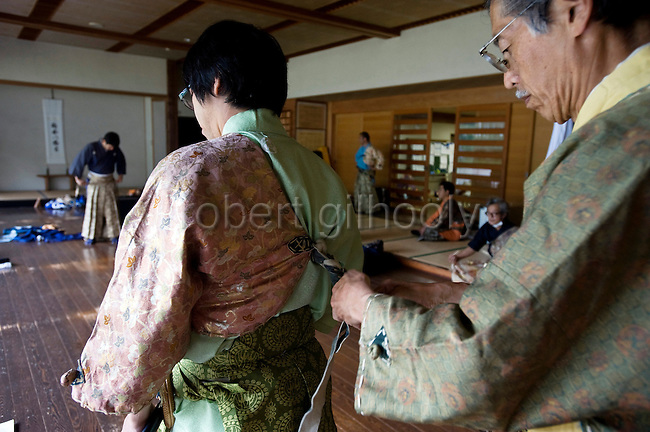 "Kaoru Murata  is given a helping hand by Akimasa Matsumoto to don  traditional attire prior to the ""yabusame-shinji"" horseback archery ritual on the final day of the Reitaisai grand festival at Tsurugaoka Hachimangu shrine in Kamakura, Japan on  14 Sept. 2012. The yabusame ritual is performed by members of the Ogasawara school, which began mounted archery rituals in the 12th century. .Yabusame was originated in middle of 6th century as a Shinto ritual. Today there are various styles and manners of Yabusame inherited by different shrines and particular families. It was common in the ancient past that the result of Yabusame depended on the number of targets successfully hit, and also fragments of the target were used to tell fortunes. The target and arrows used in successful shots were kept as amulets. The initiation of Yabusame in Tsurugaoka Hachimangu was 1186. Photographer: Robert Gilhooly"