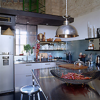 A chrome pendant light hangs from the double-height kitchen ceiling over the stainless steel breakfast bar in the kitchen