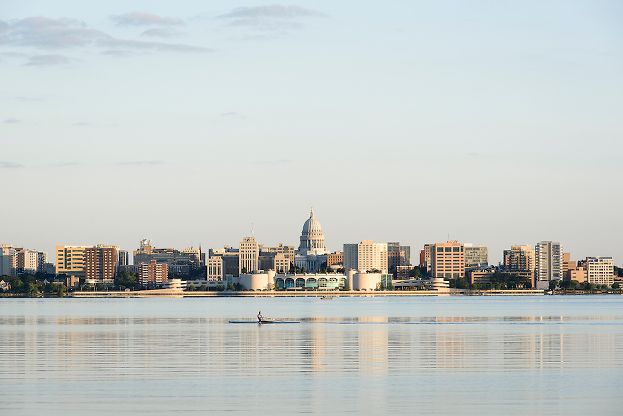 The morning sun shines on Lake Monona and the downtown Madison, Wis., skyline as a rower crosses the water during a summer sunrise on Aug. 4, 2015. On the horizon at center are the Wisconsin State Capitol and Monona Terrace Community and Convention Center. (Photo by Jeff Miller - www.jeffmillerphotography.com)