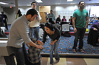 Sherry Zikria, 29, of Alexandria, Virginia who immigrated to the U.S. as a toddler, gives a high five to four year old Afghan-American Omid Gish with the help of Omar Sherzai, 28, a first generation Afghan-American of Arlington, Virginia after Gish delivered a strike in the Afghan Bowling Tournament in Annandale, Virginia on February 28, 2010.