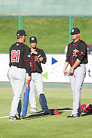 Michael De La Cruz #12, Jairo Labourt #47 and pitching coach Jeff Ware #21 of the Vancouver Canadians prior to a game against the Everett AquaSox at Everett Memorial Stadium in Everett, Washington on July 9, 2014.  Everett defeated Vancouver 9-4.  (Ronnie Allen/Four Seam Images)