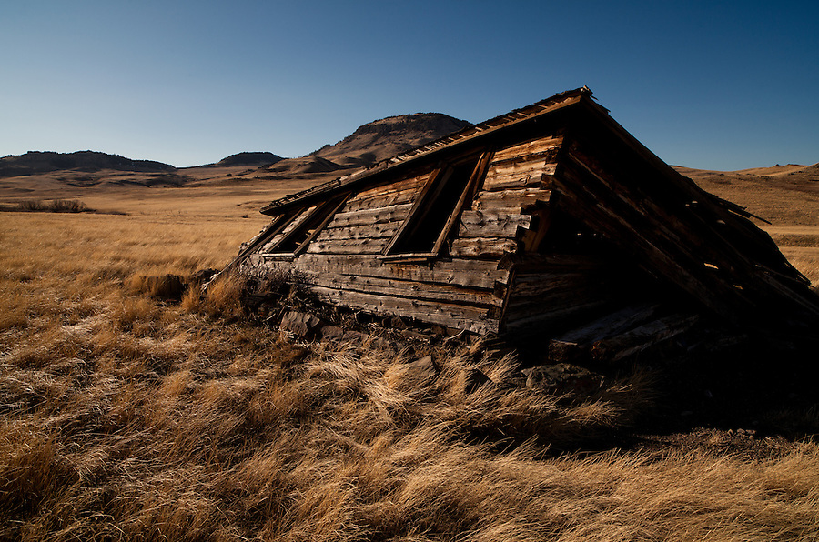 A hand-cut log cabin leans in partial collapse as gravity slowly wins its battle against the aging structure in Cascade County, Montana.