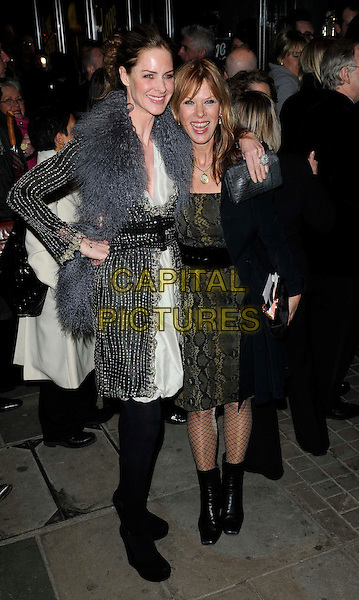 TRINNY WOODALL & NETTY MASON.The world premiere of 'Love Never Dies', Adelphi Theatre, London, England. .March 9th, 2010 .full length grey gray sheepskin fluffy fur black white dress tights wedges low cut scarf beaded crystals green gold pattern belt .CAP/CAN.©Can Nguyen/Capital Pictures.