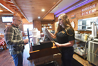 Chris Kauffman picks up a take-out order on Tuesday March 24 2020 from employee Debra Patton at Smokin' Joe's Ribhouse in Rogers. Go to nwaonline.com/200325Daily/ to see more photos.<br />(NWA Democrat-Gazette/Flip Putthoff)