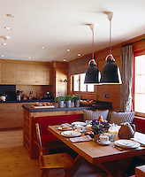 The wood-clad kitchen-diner of the chalet has been given a modern twist with granite work surfaces