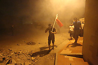 Photographer: Rick Findler..21.04.13 A protester carrying the Bahraini flag walks away from tear gas on the front lines of a clash between police and protesters in Ma'ameer, Bahrain. The number of protests in Bahrain increase dramatically during the sporting event to help bring attention to the ruling bahraini Sunni royal family's many human rights abuses and repression of the country's Shiite people.