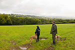 A boy and a man stand with their hunting dogs in the countryside in Wales, the United Kingdom.