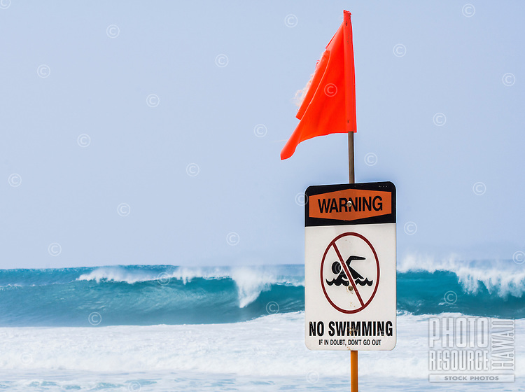 "Ocean waves break behind a ""No Swimming"" warning sign and red/orange flag posted at a beach along the North Shore of O'ahu."