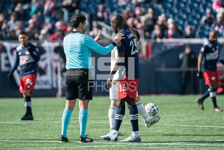 FOXBOROUGH, MA - MARCH 7: Ref Fotis Bazakos warns Wilfried Zahibo #23 of New England Revolution after a tackle during a game between Chicago Fire and New England Revolution at Gillette Stadium on March 7, 2020 in Foxborough, Massachusetts.