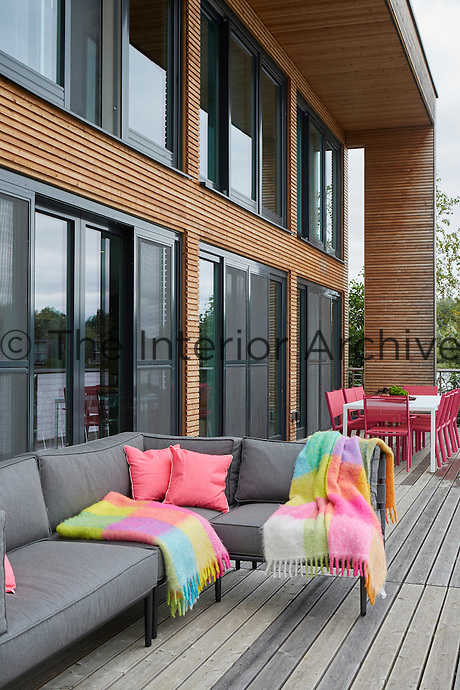 A decked terrace is a perfect spot to relax on sunny days. Bright pink dining chairs, cushions and woollen throws add spots of vibrant colour.
