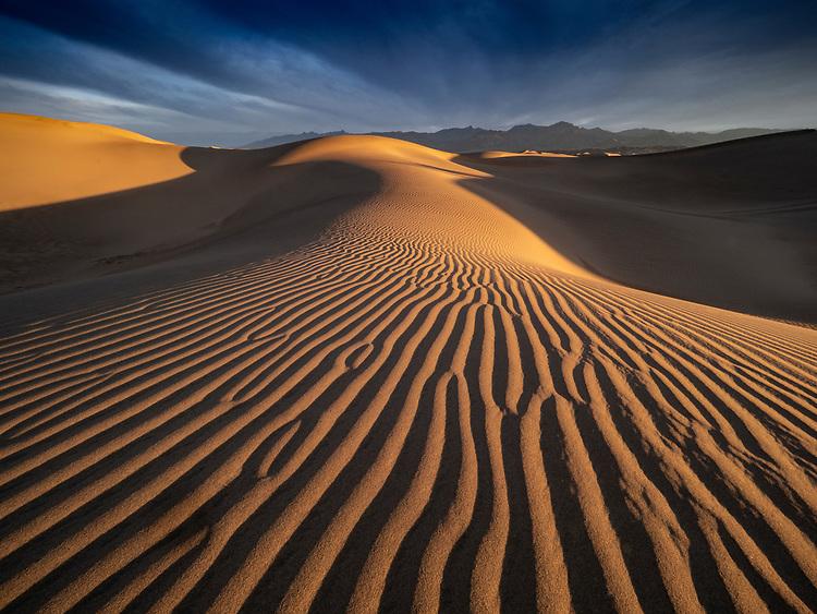 Storm light at sunrise illuminates the Mesquite Flats Sand Dunes in Death Valley National Park, California