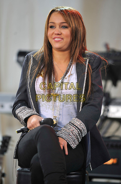 MILEY CYRUS.Miley Cyrus performs on Good Morning America held at The Chevy Stage at the Sommet Center, Nashville, Tennessee, USA..November 12th, 2008.half length 3/4 stage concert live gig performance music black jacket trousers silver cuffs trim necklaces sitting legs crossed .CAP/ADM/LF.©Laura Farr/AdMedia/Capital Pictures.