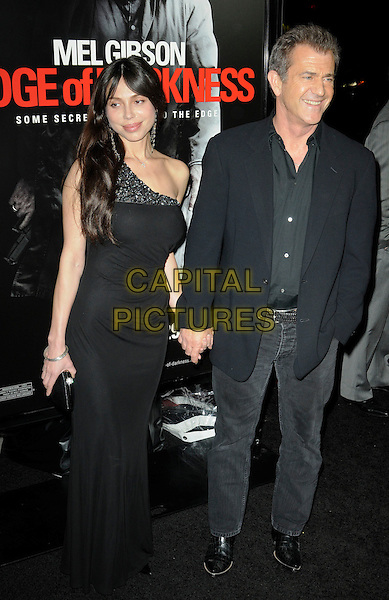 "OKSANA GRIGORIEVA & MEL GIBSON.The Los Angeles premiere of ""Edge of Darkness"" at Grauman's Chinese Theatre in Hollywood, California, USA..January 26th, 2010.full length one shoulder dress jeans denim shirt jacket holding hands black couple .CAP/ROT.©Lee Roth/Capital Pictures"