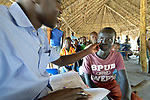 A young man is examined by nurse Ezuma Rhone in an outreach clinic in the Rhino Refugee Camp in northern Uganda. As of April 2017, the camp held almost 87,000 refugees from South Sudan, and more people were arriving daily. About 1.8 million people have fled South Sudan since civil war broke out there at the end of 2013. About 900,000 have sought refuge in Uganda. <br /> <br /> The clinic was sponsored by Global Refuge International, which receives support from the Global Health Program of The United Methodist Church. <br /> <br /> Because of the nature of the Rhino Camp, where refugees are spread out over a wide area, it's not possible for many of them to access health care, so Global Refuge International holds outreach clinics on a regular basis through several areas of the camp.