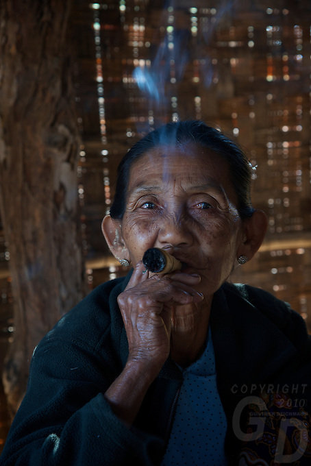 Old women from the Traditional Minnanthu Village near Bagan, smoking the traditional cheerot cigar. Myanmar/Burma