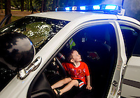 NWA Democrat-Gazette/JASON IVESTER <br /> Syrus (cq) Beagle, 2, of Bella Vista plays with the lights and sirens switches on Tuesday, Aug. 4, 2015, inside a Bella Vista Police car at Riordan Hall in Bella Vista. The police department hosted the Night Out event which featured free games and food for families.