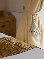 A detail illustrating one of a pair of large tasselled tie-backs on the curtains of the master bedroom