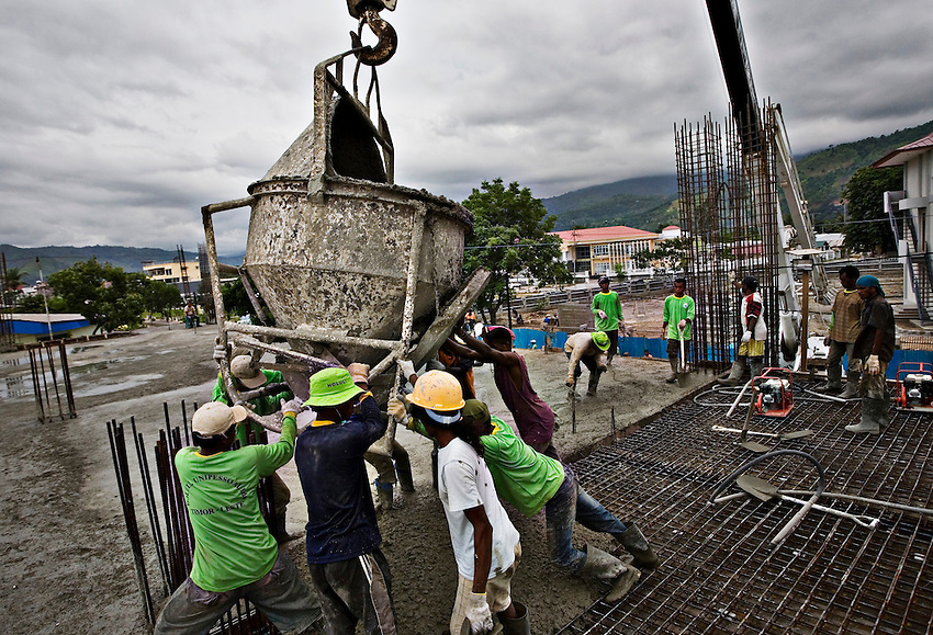 East Timorese and Indonesian construction workers pour cement into the framework of a Ministry of Defense government building in Dili, East Timor, January 8, 2010. A common joke in Dili is that each of the government ministries is getting a new building, but still none of them have any programs.