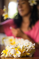 Young local woman making a plumeria lei