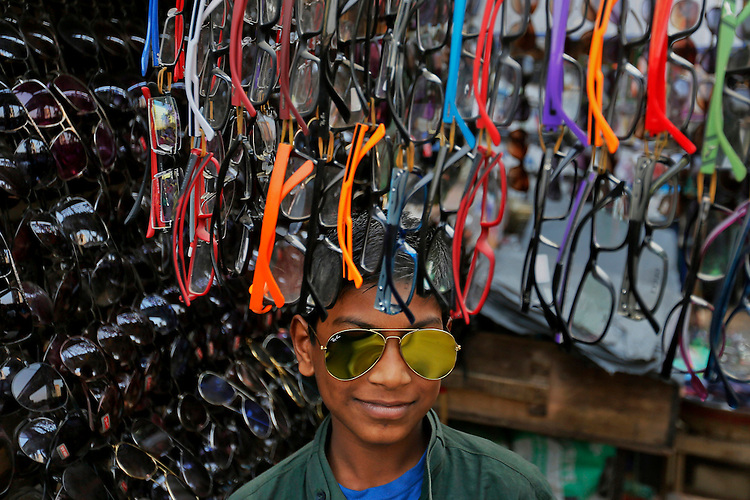 A Bangladeshi young boy reacts to the camera, as he wears a sunglass to attract customers and stand in front of his shop by the side of a road in Dhaka, Bangladesh.