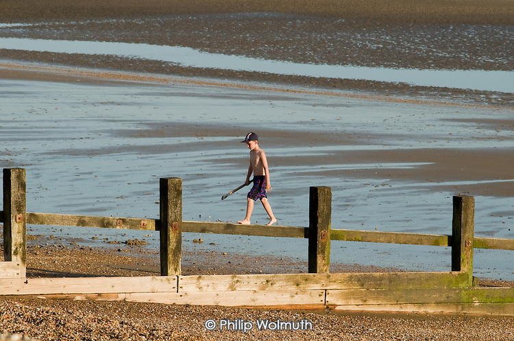 A young boy on the beach at Camber Sands, Kent