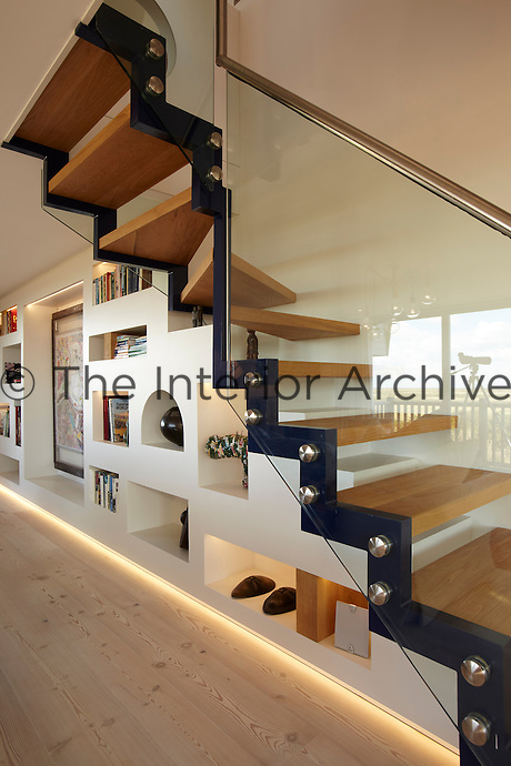 The illuminated understairs storage creates an organised and clean looking space for displaying books and artwork