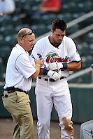 Fort Myers Miracle designated hitter Chad Christensen (12) is helped off the field by trainer Alan Rail after getting hit in the head by a foul ball while on deck during a game against the St. Lucie Mets on April 19, 2015 at Hammond Stadium in Fort Myers, Florida.  Fort Myers defeated St. Lucie 3-2 in eleven innings.  (Mike Janes/Four Seam Images)