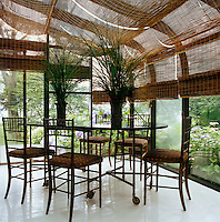 The glass ceiling and walls of the conservatory are covered with long bamboo blinds