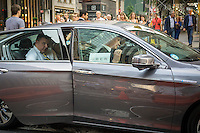 Riders climb into an Uber livery in Midtown Manhattan in New York on Tuesday, July 7, 2015. According to a survey by the Committee for Taxi Safety over half the respondents preferred Uber over taxis on price. Uber beat taxis on convenience, ease of payment and waiting time also.  (© Richard B. Levine)