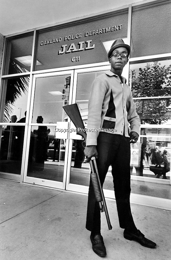 Black Panther Bobby Hutton standing in front of the Oakland Police Dept. Jail holding shotgun. Hutton was shot and killed months later in a shootout with Oakland Police. (photo by Ron Riesterer: copyright 1967)