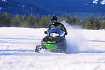 A snowmobile crosses a wide open field in southwest Montana