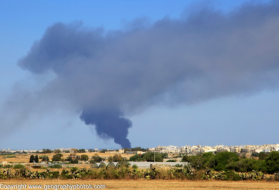 Smoke clouds atmospheric pollution from large fire at recycling centre, Malta, 22 May 2017