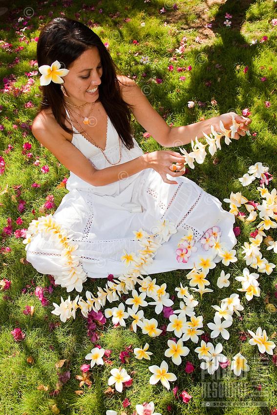 Beautiful Hawaiian woman making a fragrant plumeria lei on the lawn
