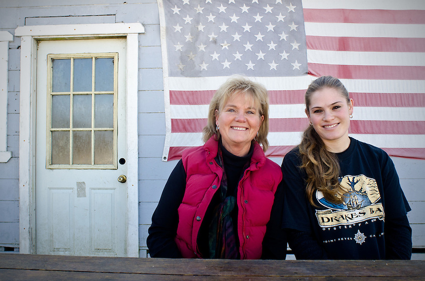 Farm manager Ginny Cummings and her niece Brigid Lunny pose for a photograph in front of a flag-draped storage building at Drakes Bay Oyster Company in Inverness, California on December 13, 2011. The Lunny Family owns and operates Drakes Bay Oyster Company and has been farming for four generations. The federal contract under which the Drakes Bay Oyster Company operates has recently expired. Now the Department of the Interior must decide whether or not to allow the sustainable oyster farm to continue commercial operations in a federally designated marine wilderness.