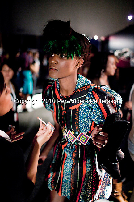 CAPE TOWN, SOUTH AFRICA - AUGUST 13: A model's hair and makeup is checked before a show with Stoned Cherrie, a fashion label, at the African Fashion International Cape Town fashion week on August 13, 2010, at the Cape Town International Convention Center, in Cape Town, South Africa. Stoned Cherrie is founded by Nkhensani Nkosi, age 37, a mother of four and a celebrated fashion designer, entrepreneur, television personality and an actress in South Africa. She launched her new collection Love Movement at this event. (Photo by Per-Anders Pettersson)