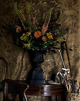 An almost Victorian looking still life of a bouquet of flowers on the hall table, displayed with an array of antique walking canes