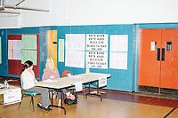Poll workers are seen as people vote in the Massachusetts Primary at the Holy Name Parish Hall polling place on Super Tuesday in West Roxbury, Massachusetts, on Tue., March 3, 2020.