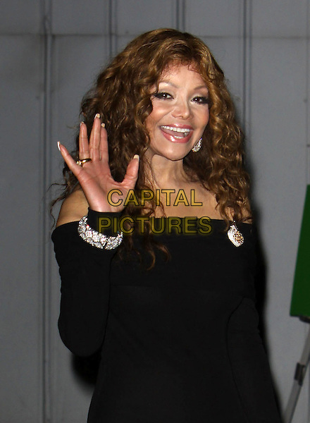 LATOYA JACKSON.27th Annual Macy's Passport Fashion Show Benefit_Show held At Barker Hangar, Santa Monica, California, USA..September 24th, 2009.half length black off the shoulder dress diamond bracelet brooch hand palm waving smiling .CAP/ADM/KB.©Kevan Brooks/AdMedia/Capital Pictures.