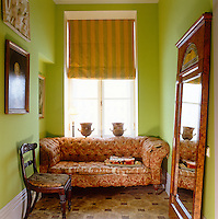 A clear sense of colour has created harmony between three disparate elements of a floral sofa, geometric parquet flooring and a striped blind in this intimate corner of a St Petersburg living room